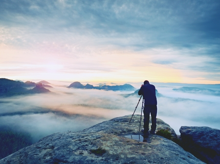 Photo artist in work. Photographer in rocky mountains. Traveller takes photos of dreamy majestic landscape, sunset at horizon Stock Photo