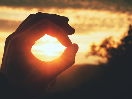 Man hand touch Sun. Fingers circle. Misty daybreak in a beautiful hilly landscape .  Lens defects.