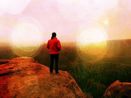 Abstract effect. Man hiker  at mountain peak. Marvelous daybreak in autumn misty landscape. Sun hidden in clouds above horizon. Stock Photo