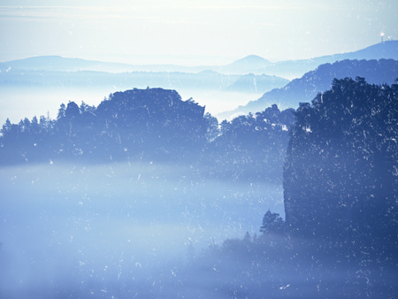 Abstract effect. Misty view into beautiful valley of Saxony Switzerland. Sandstone peaks increased from heavy fog