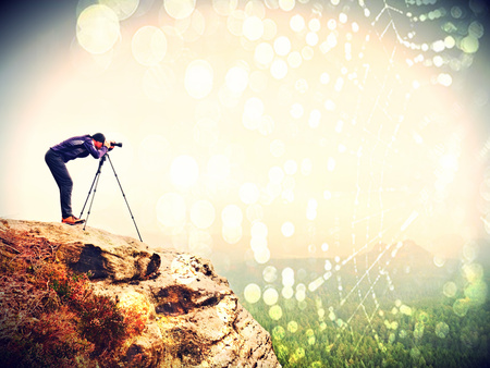 Abstract effect. Nature photographer prepare camera to takes impressive photos of misty fall mountains. Tourist photographer