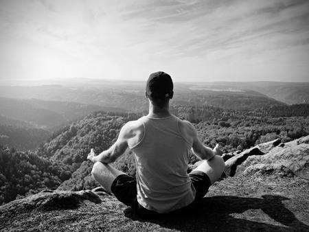 Le randonneur de corps mince en singulet vert et short noir s?asseoir sur un rocher, admirer le paysage naturel. Découvre dans la vallée de la forêt avec des collines à l'horizon.
