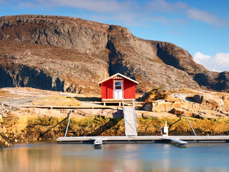 Rural Norwegian landscape, traditional red and white wooden house on rocky island. Suny spring day with smooth water level in bay.