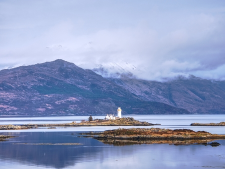 Iasle Ornsay Lighthouse built on a small islet  located on the ferry route. Low level of smooth water. Snowy mountain peaks hidden in cloudy background.