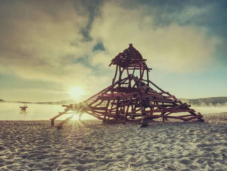 Wooden playground attraction for children in swimming bay.  Pirate ship with tower built in sand of holiday resort.  Calm water of lake.