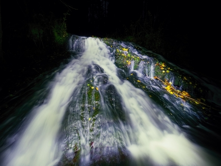 Night waterfall. White water spray in waterfall on stream, foamy water is falling over mossy rock. The spray create on level and gravel milky water Stock Photo