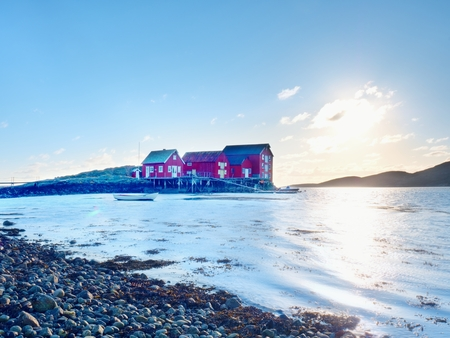 Norway fishing village on stony island. Shinning red white houses in quiet bay. Smooth water level mirroring clear cyan sky. Stock Photo