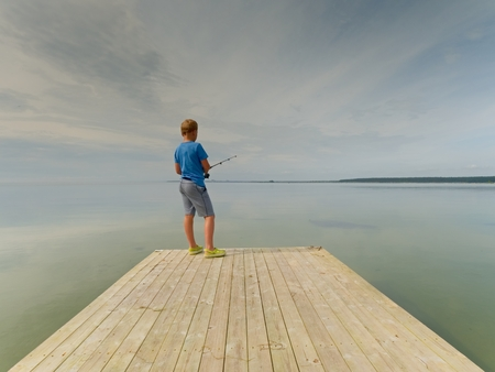 Small blond hair boy is fishing at the end of wooden mole. Smooth water level in bay, clear sky. Kid in blue t-shirt, grey striped shorts and green flip-flops