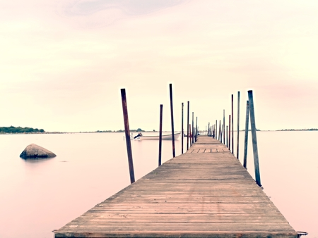 Empty wooden mole in water of blue lake.  Old fishing wharf for hired boats and swimmers. Waves smooth by long exposure, cloudy sky. Stock Photo