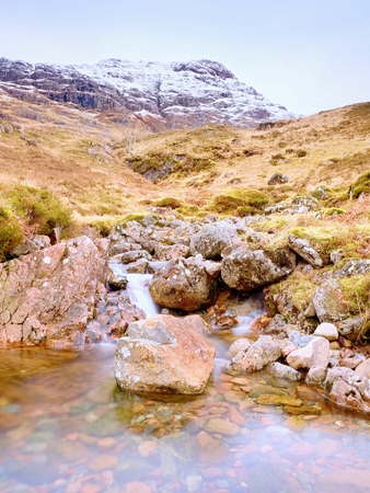 The rough mountain stream in the mountains. Snowy cone of mountain in clouds. Dry grass and heather bushes on banks