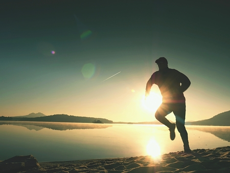 Exercising on the lake beach at sunset, big sun at horizon Stock Photo