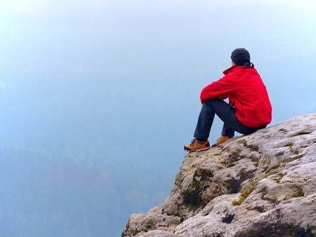 Thinking man sit on rock. Man on view point  of exposed peak watching to misty far distance. Cold day in mountains. Stock Photo