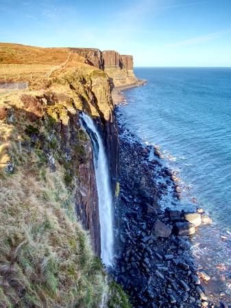 Kilt Rock Waterfall in winter midday. Kilt rock coastline cliff and waterfall in Scottish highlands, Scotland, United Kingdom
