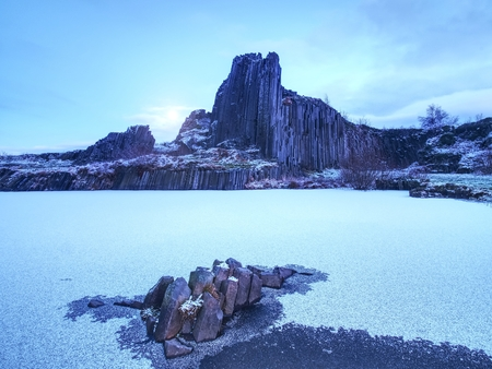 Peak of basalt pillars covered by snow, frozen pool. Full moon in blue sky in the background. The winter begun