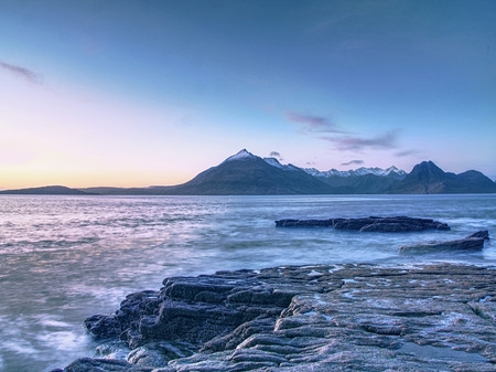Rocky coastline in Elgol at sunset with cracked rocks in detail, Isle of Skye, Scotland. Blue shadows of cold February afternoon, clear sky.