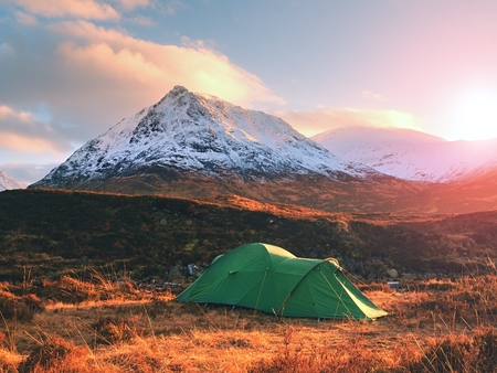 Green tent and snowy mountain peak. Higland in Scotland an marvelous sunny winter day. Dry grass and heather bushes. Hikers tent Stock Photo