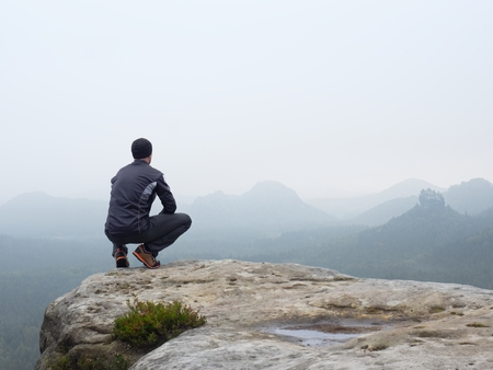 Adult tourist in black trousers, jacket and dark cap sit on cliff's edge and looking to misty hilly valley bellow