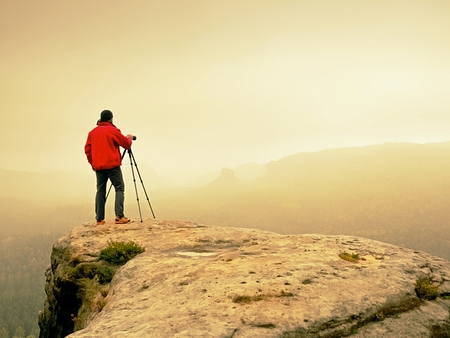 Professional photographer on location takes photos with mirror camera on peak of rock. Dreamy foggy landscape, spring orange pink misty sunrise in a beautiful valley below.