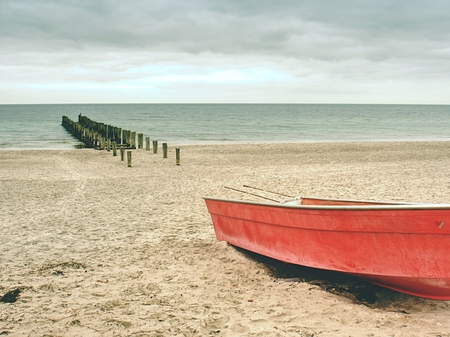 Abandoned red paddle boat on sandy beach of sea.  Smooth water level within morning windless. Dramatic and picturesque scene.