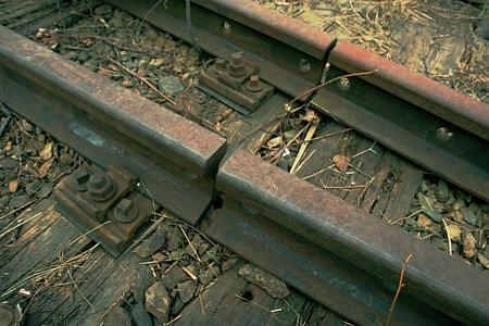 Detail of old rusty rails in abandoned railway station.  Rusty train railway detail, granite stones between rails