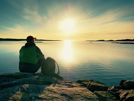 Young man sitting on a rock watching a gorgeous sunset on the sea.  Hiker alone enjoy evening at autumnal offshore.