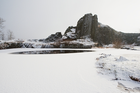 Winter basalt formation Panska skala, close Kamenicky Senov in Czech Republic. Exposed basalr poles of burned out volcano.
