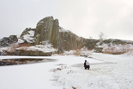 Outdoor photographer takes photo of snowy Panska rocks formation, National Park Czech Switzerland, Czech Republik