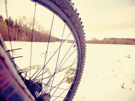 Winter snow riding on mountain bike. Extreme weather, slippery road in field, close low ankle wide view to front wheel.