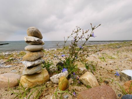 Stacked stones in pyramid on the grass. Coastline in summer