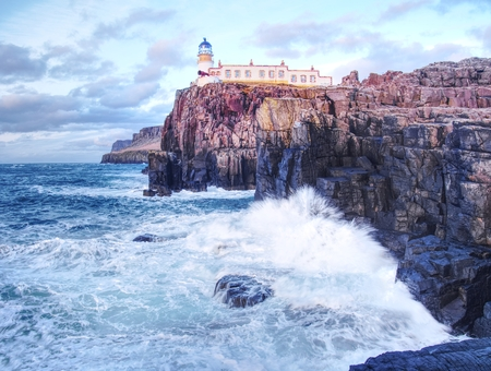 Famous view to Neist Point lighthouse on the end of  world. Foamy evening blue sea strikes against the sharp cliff.  The Isle of Skye, Scotland