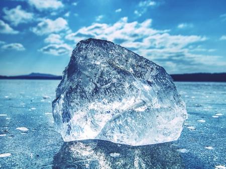 Témpano de hielo en la superficie congelada con mucha reflexión, cielo azul en fondo. Lago helado de invierno Foto de archivo