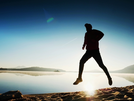 happy man running and jumping alone on the beach at sea Stock Photo