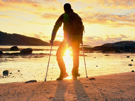 Disabled hurt hiker man is  celebrate alone attachment of his target. Tourist  stand or walk along sea water