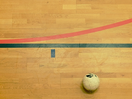 Red and black line marks and football balll on hardwood sporting floor.  Worn out wooden floor of sports hall with colorful marking lines Фото со стока