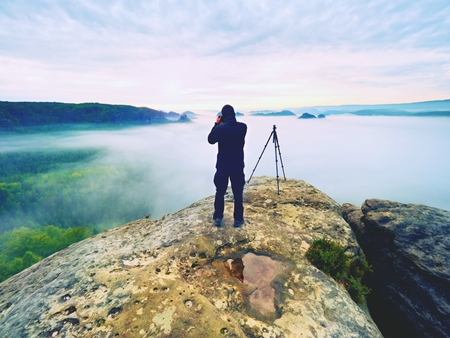 Photo artist in work. Photographer in rocky mountains. Traveller takes photos of dreamy majestic landscape, sunset at horizon Archivio Fotografico