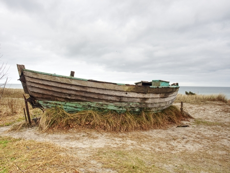 Wrecked wooden fisher boat. Broken abandoned boat in sand of sea bay. Wheatered wood and rusty meatal parts  Stock Photo