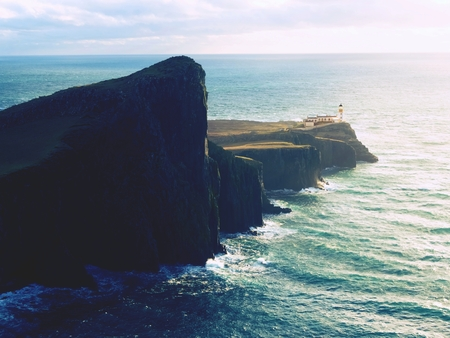 Neist Point lighthouse on rocky cliff above wavy sea. Blue evening sea and sharp cliffs, Isle of Skye, Scotland