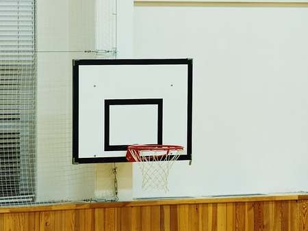 Old worn basketball hoop and white shool gym wall background. Foto de archivo