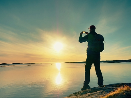 High tourist  taking selfie on mobile phone against scenic view of sea against evening sky. Sun mirror in smooth water level. Silent sea bay 版權商用圖片