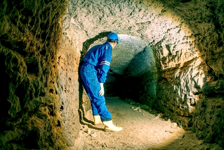 Hunched worker in a blue overall and a safety helmet work in underground tunnel. Dangerous employment.  The miner in the underground dome. The staff check the underground unsupported  mine.