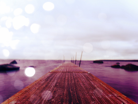 Abstract effect. Wet wooden pier in smooth water of sea bay.  Old mole anchored with steel poles into bottom. Iron ladder for passangers and swimmers.