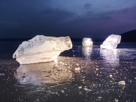 Detail view into  an ice with deep scratches and cracks. Cut floe against to evening sky and spot light. Stock Photo