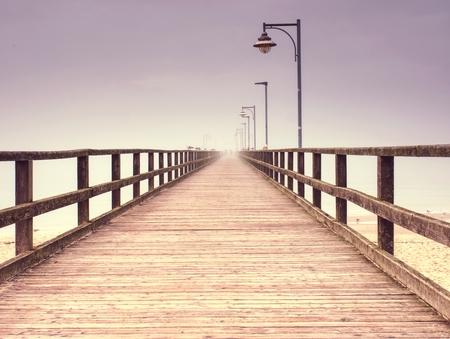 Empty wooden pier in harbor. Steel lamp post, horizon hidden in thick fog. Autumn mist on beach bridge  above sea