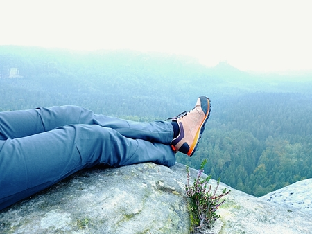 Man hiker climb rock on mountain peak cliff and take a rest.  Concept of sport and active life. Freedom concept Stock Photo