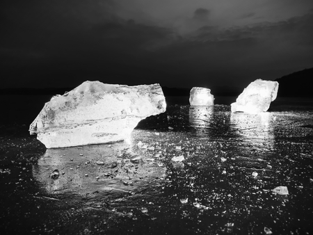 Cut ice. Crushed cubes lighted with strong backlight.  Silent bay  with flat frozen level.  The light spectre in ice.