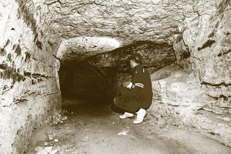 Miner man underground in a mine tunnel.  Worker in overalls, safety helmet and gummy boots is busy with work. Solarize effect