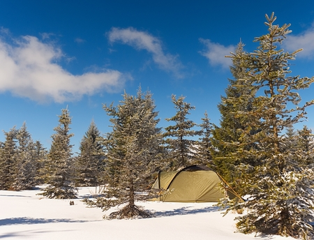 Tent in winter landscape. Trekking tent, poles, red  snowshoes on snow between trees in the mountains. Nice sunny winter day. Stock Photo