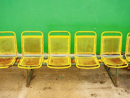 Vintage steel seats on outdoor stadium players bench chairs with worn paint below green wall Stock Photo