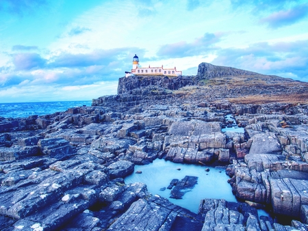 Old lighthouse on the end of thin spit of land. Sharp rocky cliff aganst to foamy ocean, evening blue sky. Stock Photo