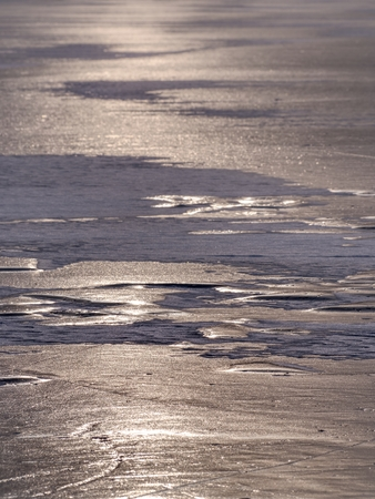 Melting ice tip of the iceberg. The sun shines through cracks and create interesting reflections.. Stock Photo